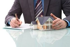 Man with model home signing a contract